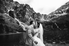 De bruidegom die zijn jonge bruid, op de kust van het meer Morskie Oko kussen polen De Zwart-witte foto van Peking, China royalty-vrije stock afbeelding