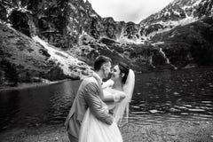 De bruidegom die zijn jonge bruid, op de kust van het meer Morskie Oko kussen polen De Zwart-witte foto van Peking, China stock fotografie