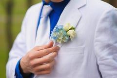 De bruidegom draagt boutonniere stock afbeelding