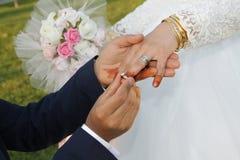 De bruidegom draagt bruid op ring stock fotografie