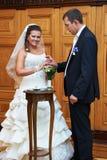 De bruidegom draagt een trouwring een gelukkige bruid Stock Foto