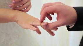 De bruidegom draagt op de vinger van de bruid dichte omhooggaand van de huwelijksslijtage stock videobeelden