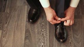 De bruidegom draagt schoenen stock videobeelden