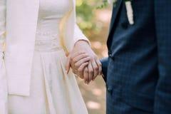 De bruidegom in een blauw kostuum en de bruid in een huwelijkskleding houden elke anderen overhandigen De handen sluiten omhoog royalty-vrije stock foto's