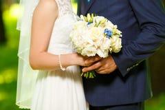 De bruidegom in een kostuum en de bruid in witte kledings bevindende partij houden langs boeketten van bloemen Stock Foto's