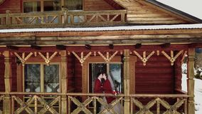 De bruidegom en de bruid drinken koffie op een balkon van het houten plattelandshuisje van het logboekchalet in dorp terwijl de h stock footage