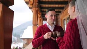 De bruidegom en de bruid drinken koffie of thee uit koppen op een balkon van het houten plattelandshuisje van het logboekchalet i stock video