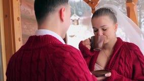 De bruidegom en de bruid drinken koffie of thee uit koppen op een balkon van het houten plattelandshuisje van het logboekchalet i stock videobeelden