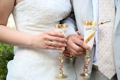 De bruidegom en de bruid houden glazen Royalty-vrije Stock Foto's