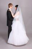 De bruidegom en de bruid omhelzen en bekijken elkaar Stock Foto's
