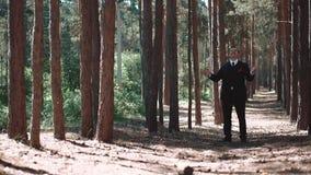 De bruidegom ervaart een betekenis van vreugde en een vervulde opdracht, na het huwelijk, die zich in het bos bevinden dat hij he stock videobeelden