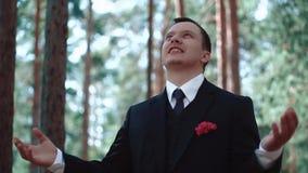 De bruidegom ervaart een betekenis van vreugde en een vervulde opdracht, na het huwelijk, die zich in een bos, langzaam close-up  stock video