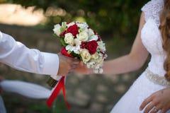 De bruidegom geeft bruidboeket Royalty-vrije Stock Afbeeldingen