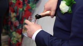 De bruidegom giet champagne stock footage