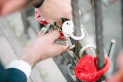 De bruidegom hangt het kasteel op de brug voor de jonggehuwden De huwelijkstraditie stock afbeeldingen