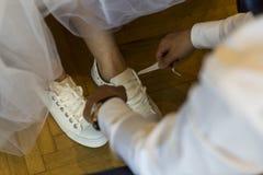 De bruidegom helpt de bruid haar pantoffels zetten en haar binden stock fotografie