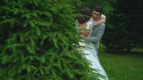 De bruidegom houdt de bruid in haar wapens De bruid lacht helder in de handen van de bruidegom stock videobeelden