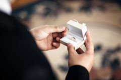 De bruidegom houdt een doos van de juwelengift met gouden trouwringen Royalty-vrije Stock Foto