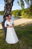 De bruidegom houdt houdend nieuwe vrouw in openluchtlandschap Royalty-vrije Stock Foto