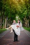 De bruidegom houdt zijn bruid in wapens en glimlachen van geluk in de zomerpark royalty-vrije stock fotografie