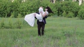De bruidegom houdt zijn bruid in zijn wapens stock video