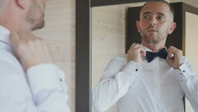 De bruidegom kleedt een vlinderdas voor spiegel stock footage