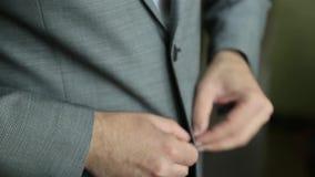 De bruidegom knoopt een jasje dicht Modieuze mens die in een kostuum vastmakende knopen op zijn jasje voorbereidingen treffen uit stock videobeelden