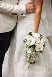 De bruidegom koestert bruid die een boeket houdt Royalty-vrije Stock Afbeelding