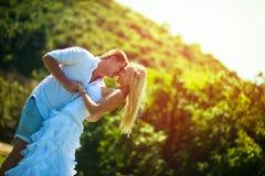 De bruidegom koestert de bruid op een hete de zomerdag stock afbeeldingen
