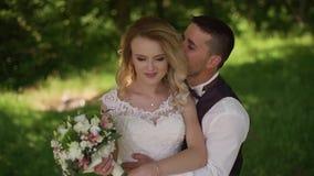 De bruidegom komt aan het charmeren van blondebruid met boeket achter haar Langzame Motie stock videobeelden