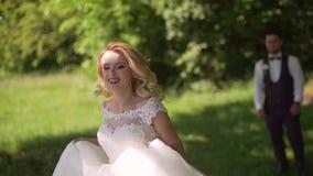 De bruidegom komt aan het charmeren van blondebruid met boeket achter haar Langzame Motie stock video