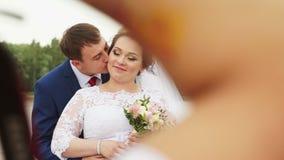 De bruidegom kust de bruid op de wang stock videobeelden
