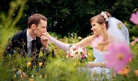De bruidegom kust de hand van de bruid Stock Afbeeldingen