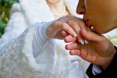 De bruidegom kust een hand van de bruid stock afbeelding