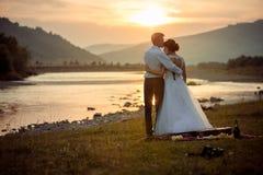 De bruidegom kust zacht zijn schitterende bruid in het voorhoofd tijdens de zonsondergang Huwelijkspicknick op de rivierbank stock foto's
