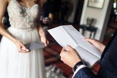 De bruidegom leest een brief aan de bruid stock fotografie