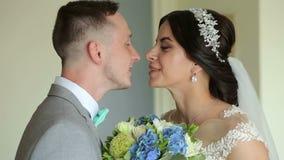 De bruidegom loopt in de ruimte aan de bruid en geeft haar boeket van bloemen stock footage