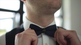 De bruidegom maakt bandvlinderdas recht stock videobeelden
