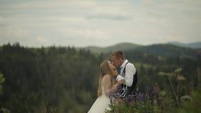 De bruidegom met bruid drinkt champagne op een bergheuvels Het Paar van het huwelijk Familie stock videobeelden