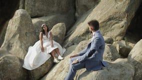 De bruidegom met bruid zit op een helling van de berg Het Paar van het huwelijk gelukkig stock video