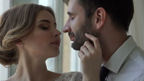 De bruidegom met de bruidtribune dichtbij een venster stock video