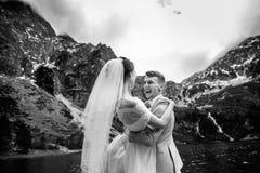 De bruidegom omcirkelt zijn jonge bruid, op de kust van het meer Morskie Oko polen De Zwart-witte foto van Peking, China royalty-vrije stock fotografie