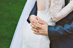 De bruidegom omhelst de bruid Stock Foto