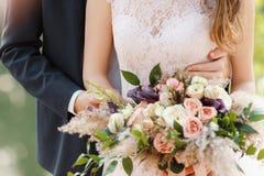 De bruidegom omhelst erachter zacht de bruid Stock Foto's