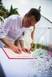 De bruidegom ondertekent documenten op registratie van huwelijk in openlucht Een jong paar ondertekent de huwelijksdocumenten De  stock foto's