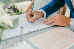 De bruidegom ondertekent de documenten van de huwelijksregistratie Jong paar dat huwelijksdocumenten ondertekent Royalty-vrije Stock Afbeeldingen