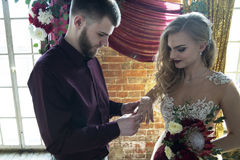 De bruidegom plaatst de ring op de bruid bij de huwelijksceremonie Stock Foto's