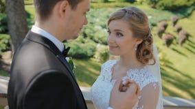 De bruidegom rekt zijn hand aan zijn bruid uit stock footage