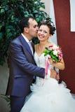 De bruidegom van de kus en gelukkige bruid Stock Afbeeldingen