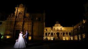 De bruidegom van de Leccebruid loopt bij nacht stock videobeelden